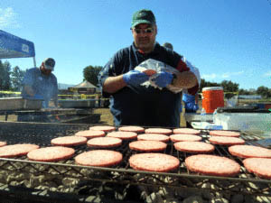 Marty Laguna, director of materials management for Saint Louise Regional Hospital, cooks burgers during a barbecue thanking first responders of the recent Loma Fire. Photo by Marty Cheek