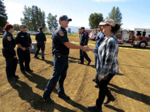 Photo by Marty Cheek Cal Fire firefighter Ryan Michaels greets Senior Executive Administrative Assistant Corrie Rudd who thanked him and all first responders for their work on the Loma Fire.